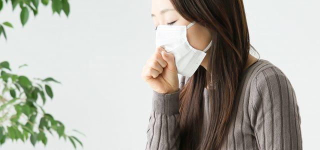 マスクをかけて咳をする女性