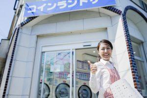 コインランドリーの店の前に立つ女性